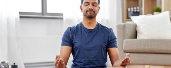 Homme pratiquant la méditation dans son salon